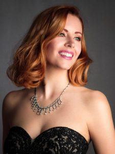 chica pelirroja de época con vestido negro y collar de diamantes